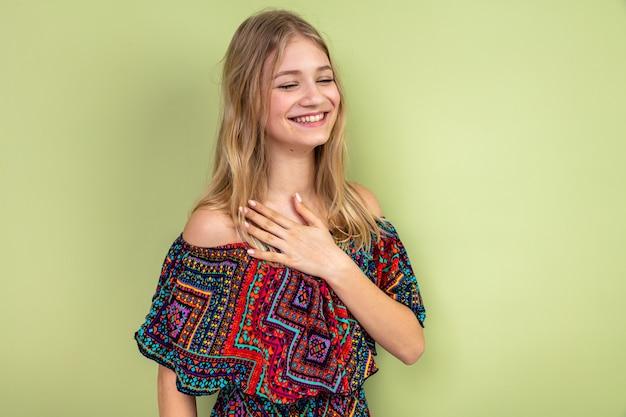 Sorridente giovane donna bionda che mette la mano sul petto e guarda di lato