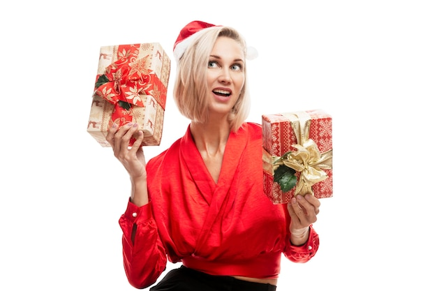 Smiling young blonde woman in santa hat and red blouse with christmas gifts in her hands. isolated