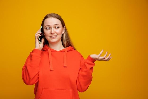빈 손을 보여주는 측면을보고 전화 통화 웃는 젊은 금발의 여자