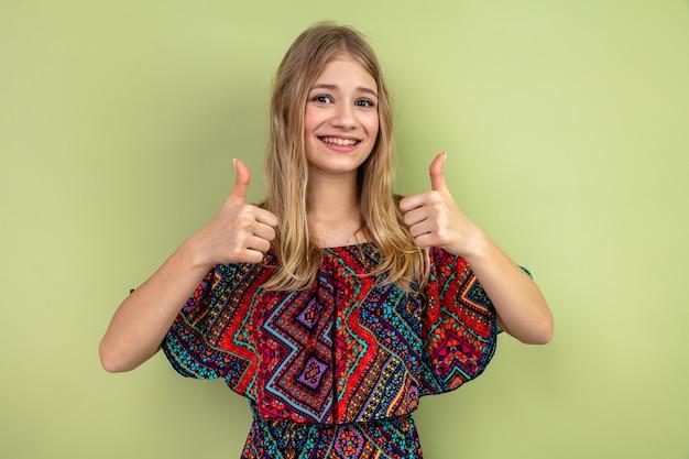 笑顔の若いブロンドの女性が親指を立てる