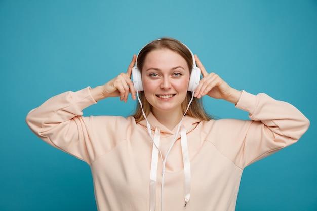 音楽を聴いてヘッドフォンを身に着けてつかむ若いブロンドの女性の笑顔