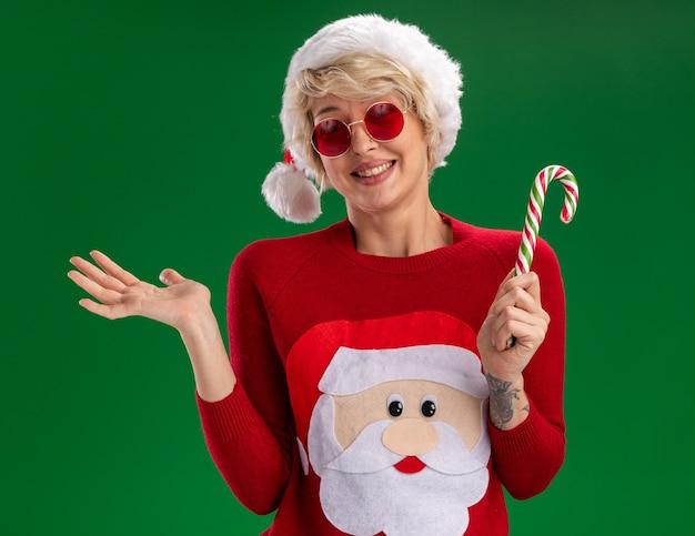 Sorridente giovane donna bionda che indossa il cappello di natale e babbo natale maglione di natale con gli occhiali che tengono il bastoncino di zucchero natalizio guardando mostrando la mano vuota isolata sulla parete verde