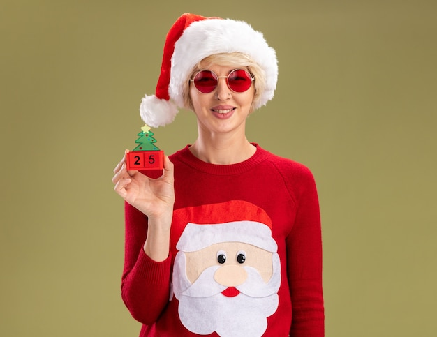 Sorridente giovane donna bionda che indossa cappello di natale e babbo natale maglione di natale con gli occhiali che tengono il giocattolo dell'albero di natale con data guardando isolato sul muro verde oliva con spazio di copia