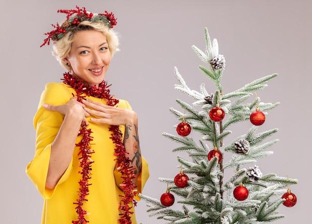 흰색 배경에 고립 된 카메라를보고 가슴에 손을 유지 장식 된 크리스마스 트리 근처에 서있는 목 주위에 크리스마스 머리 화 환과 반짝이 갈 랜드를 입고 웃는 젊은 금발의 여자
