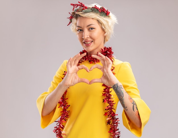 Smiling young blonde woman wearing christmas head wreath and tinsel garland around neck looking at camera doing heart sign isolated on white background