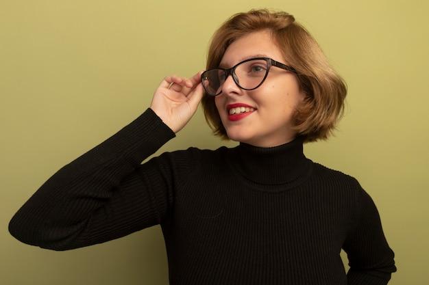 Sorridente giovane donna bionda che indossa e afferra gli occhiali guardando il lato isolato sulla parete verde oliva