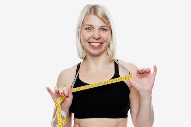 그녀의 목 주위에 테이프를 측정 하여 젊은 금발의여자가 웃 고. 스포츠와 다이어트. 흰색 배경에 고립.