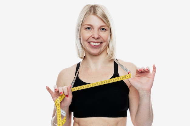 Smiling young blonde woman with measuring tape around her neck. sports and diets. isolated on white background.