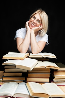 Smiling young blonde woman with a pile of books. education, knowledge and hobbies.