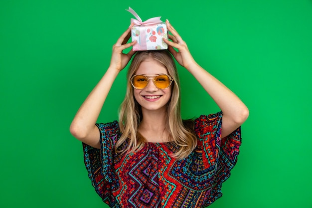 Smiling young blonde woman with sun glasses holding gift box over her head