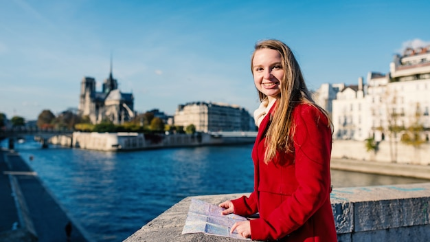 Smiling young blonde woman with with notre dame cathedral. paris, france.