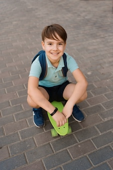 市内のスケートボード、ペニーボードに乗って白人の子供で遊ぶ少年の笑顔