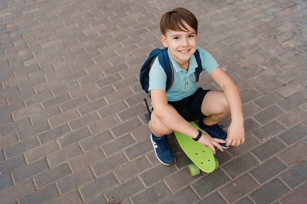 Giovane ragazzo sorridente che gioca sullo skateboard in città, bambino caucasico in sella a bordo di penny