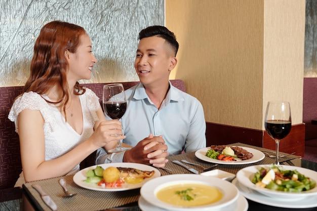 저녁 식사를 하고 식당 테이블에서 이야기할 때 손을 잡고 사랑에 빠진 젊은 남자친구와 여자친구를 웃고