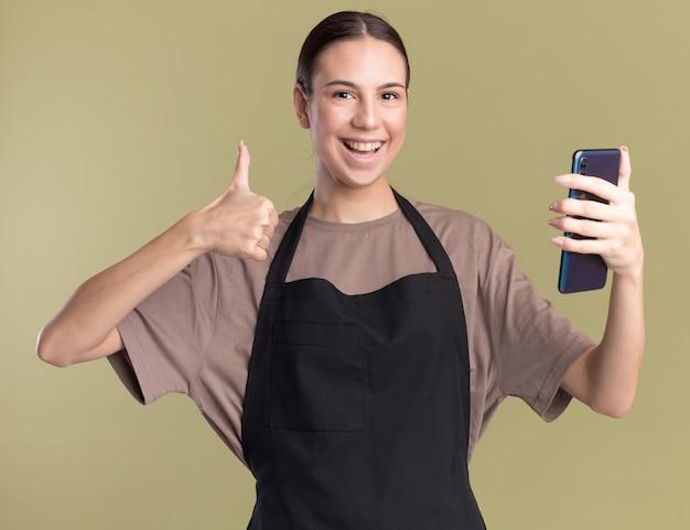制服の親指で若いブルネットの理髪師の女の子を笑顔し、オリーブグリーンで電話を保持します