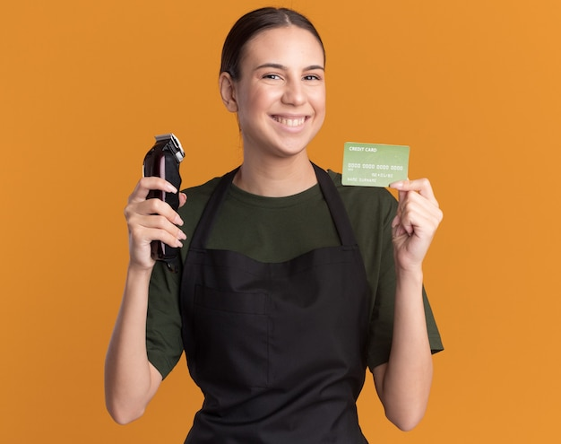 Smiling young brunette barber girl in uniform holding hair clippers and credit card isolated on orange wall with copy space