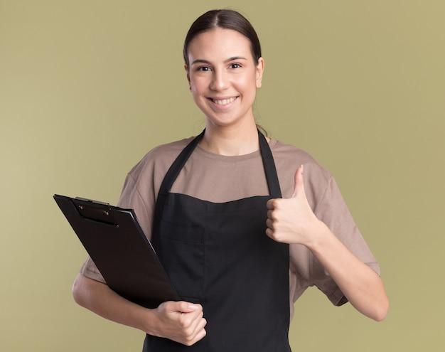 Sorridente giovane barbiere bruna in uniforme tiene appunti e pollice in alto isolato su parete verde oliva con spazio copia