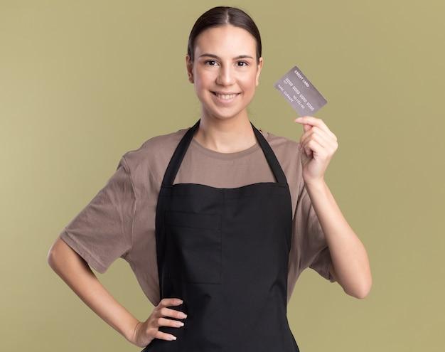La giovane ragazza sorridente del barbiere castana in uniforme tiene la carta di credito isolata sulla parete verde oliva con lo spazio della copia