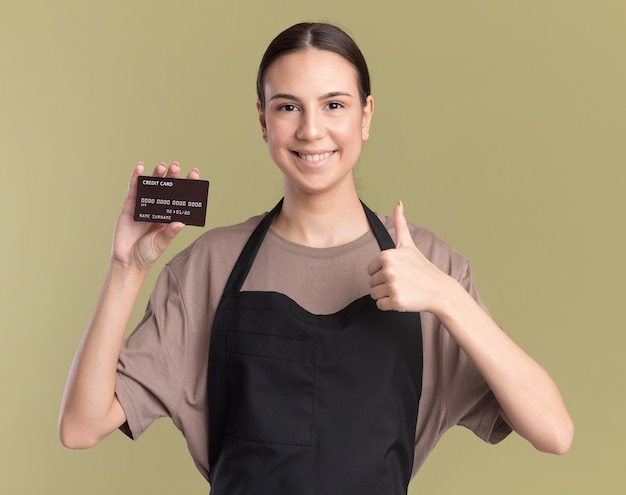 Smiling young brunette barber girl in uniform holds credit card and thumbs up on olive green