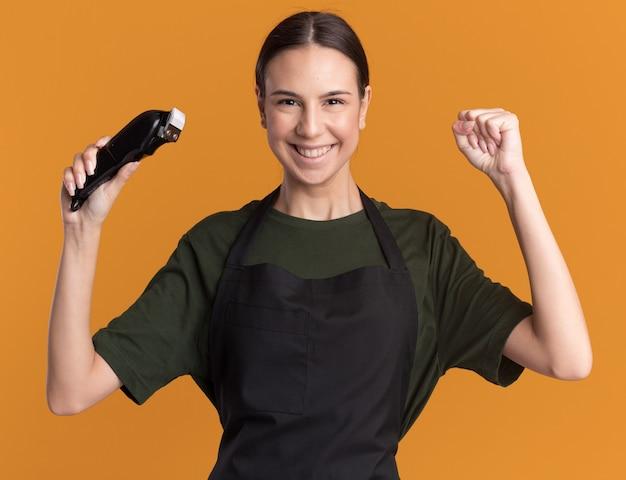 La giovane ragazza sorridente del barbiere castana in uniforme tiene il pugno e tiene i tagliacapelli isolati sulla parete arancione con lo spazio della copia