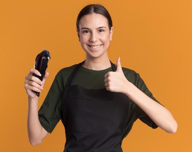 Sorridente giovane barbiere bruna in uniforme alza il pollice e tiene le tosatrici isolate sulla parete arancione con spazio per le copie