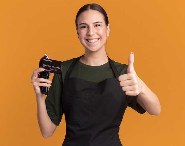 Smiling young brunette barber girl in uniform thumbs up and holds hair clippers with credit card isolated on orange wall with copy space