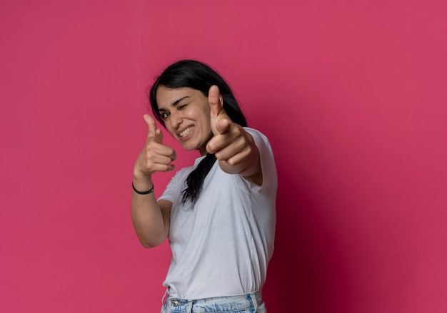 Smiling young brunette caucasian girl blinks eye and points with two hands isolated on pink wall