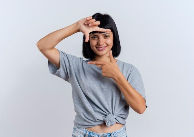 Sorridente giovane ragazza bruna caucasica gesti cornice segno della mano