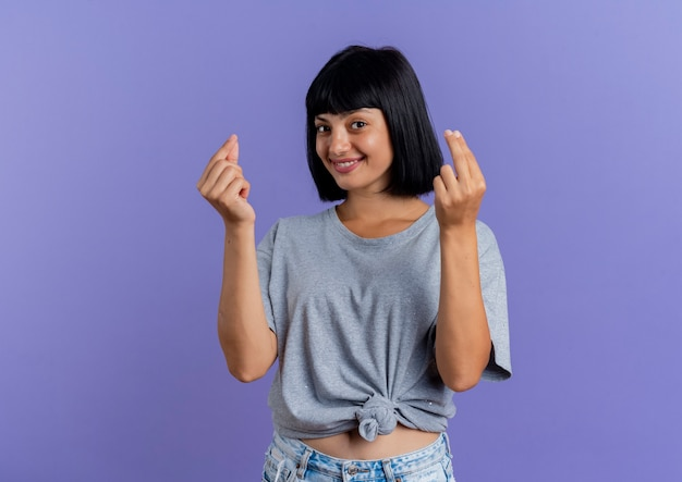 Smiling young brunette caucasian girl gestures money hand sign with two hands isolated on purple background with copy space