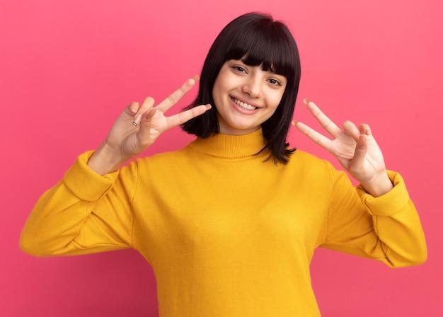 Улыбающаяся молодая брюнетка кавказская девушка жестикулирует знак победы руками на розовом
