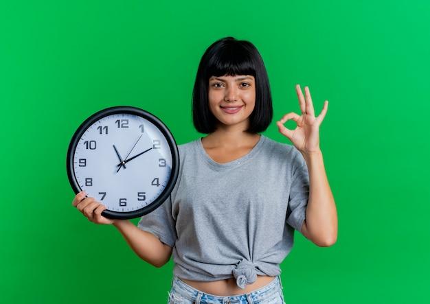 La giovane ragazza caucasica castana sorridente tiene il segno giusto della mano di gesti e dell'orologio