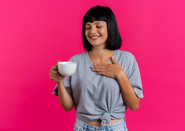 La giovane ragazza caucasica castana sorridente tiene la tazza e mette la mano sul petto