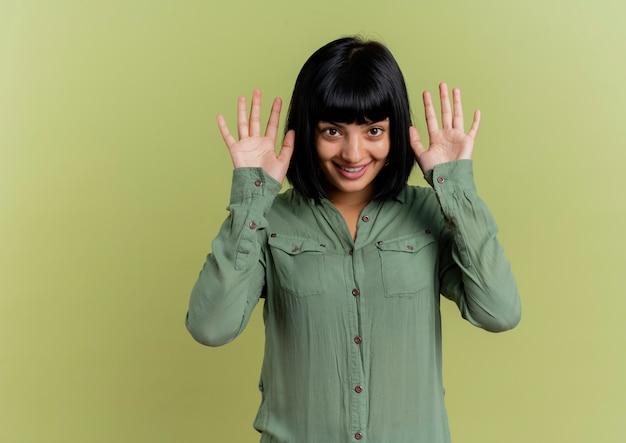 La giovane ragazza caucasica castana sorridente tiene le mani vicino alla testa isolata su fondo verde oliva con lo spazio della copia