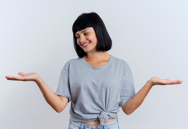 La giovane ragazza caucasica castana sorridente tiene le mani aperte che esaminano lato