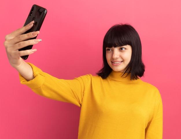 La giovane ragazza caucasica castana sorridente tiene ed esamina il telefono che prende selfie sul rosa