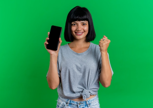 La giovane ragazza caucasica castana sorridente tiene il telefono e mantiene il pugno isolato su priorità bassa verde con lo spazio della copia