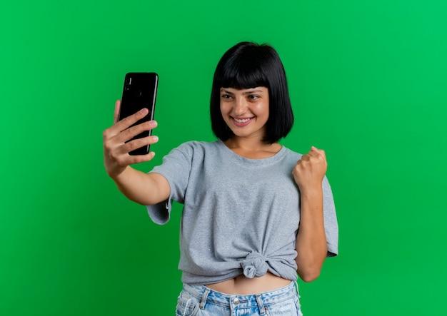 La giovane ragazza caucasica del brunette sorridente mantiene la holding del pugno e guardando il telefono isolato su priorità bassa verde con lo spazio della copia