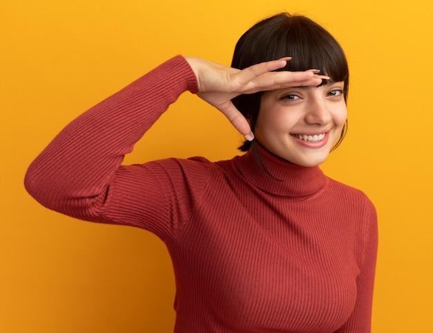 La giovane ragazza caucasica castana sorridente tiene il palmo sulla fronte isolata sulla parete arancione con lo spazio della copia