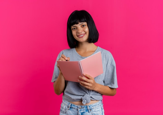 Smiling young brunette caucasian girl looks at camera and holds pen and notebook isolated on pink background with copy space