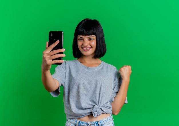 La giovane ragazza caucasica del brunette sorridente esamina il telefono e mantiene il pugno isolato su priorità bassa verde con lo spazio della copia