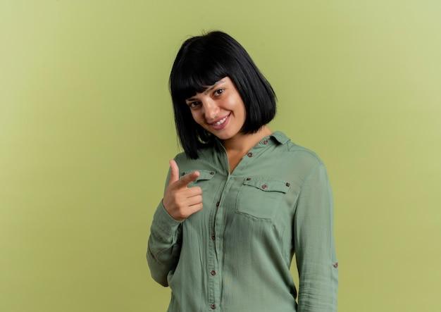 La giovane ragazza caucasica castana sorridente guarda e indica la macchina fotografica isolata su fondo verde oliva con lo spazio della copia
