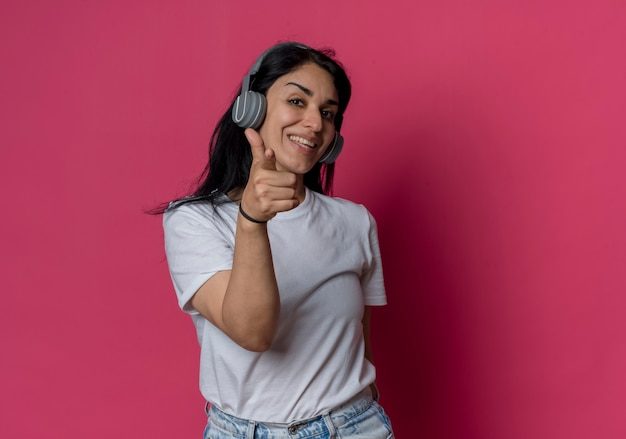 분홍색 벽에 고립 된 헤드폰 포인트에 웃는 젊은 갈색 머리 백인 여자