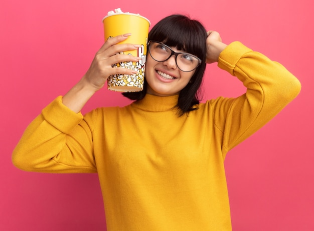 Smiling young brunette caucasian girl in optical glasses puts hand on head and holds popcorn bucket looking at side on pink
