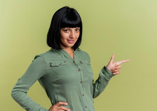 La giovane ragazza caucasica castana sorridente indica al lato che guarda l'obbiettivo isolato su fondo verde oliva con lo spazio della copia