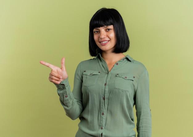 La giovane ragazza caucasica castana sorridente indica a lato ed esamina la macchina fotografica isolata su fondo verde oliva con lo spazio della copia