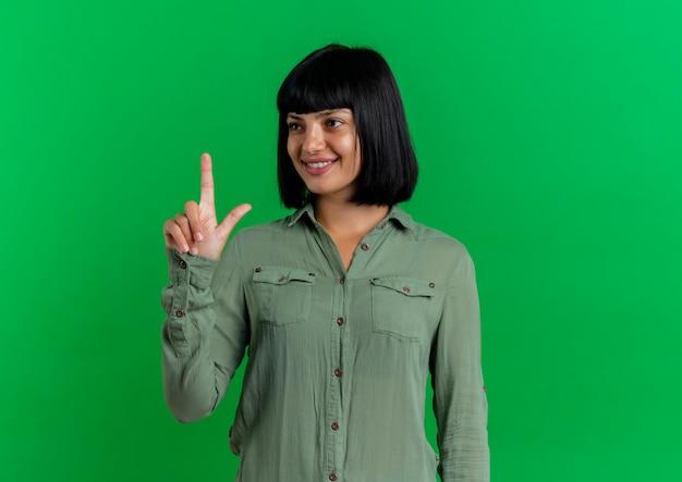 La giovane ragazza caucasica castana sorridente indica in su guardando il lato isolato su priorità bassa verde con lo spazio della copia