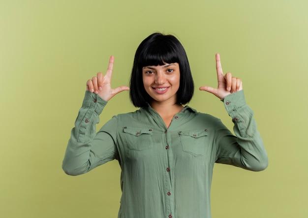 La giovane ragazza caucasica castana sorridente indica con due mani e sguardi