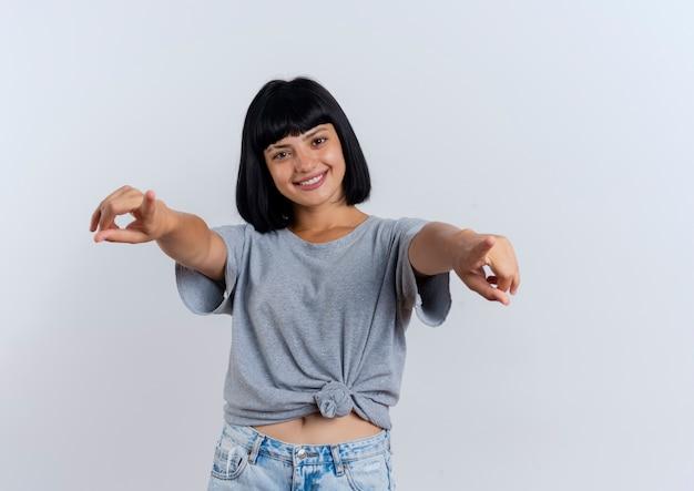 La giovane ragazza caucasica castana sorridente indica con due mani