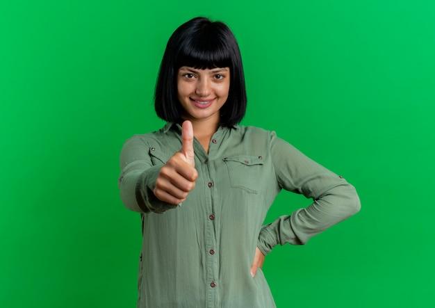 La giovane ragazza caucasica castana sorridente mette la mano sulla vita e sui pollici in su isolato su fondo verde con lo spazio della copia