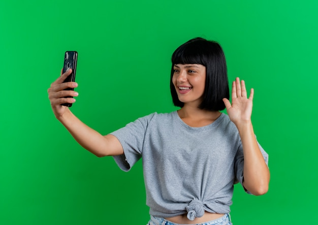 Sorridente giovane ragazza bruna caucasica alza la mano e guarda il telefono isolato su sfondo verde con copia spazio